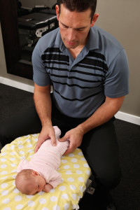 A chiropractor treating a new born baby