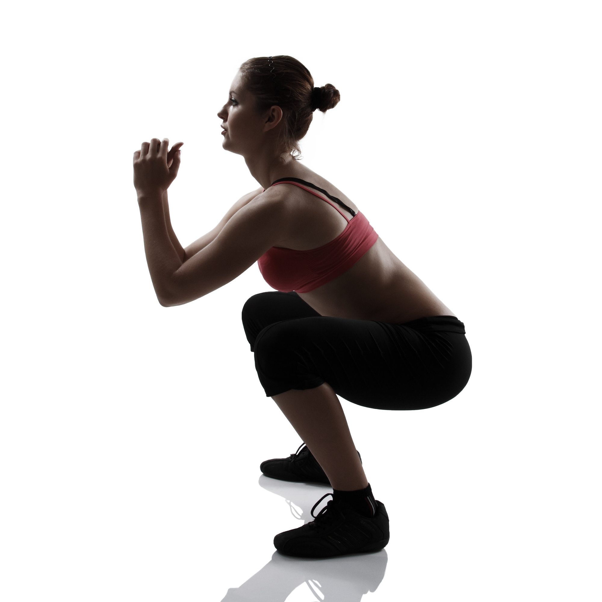 sport girl doing squatting exercise, silhouette studio shot over white background