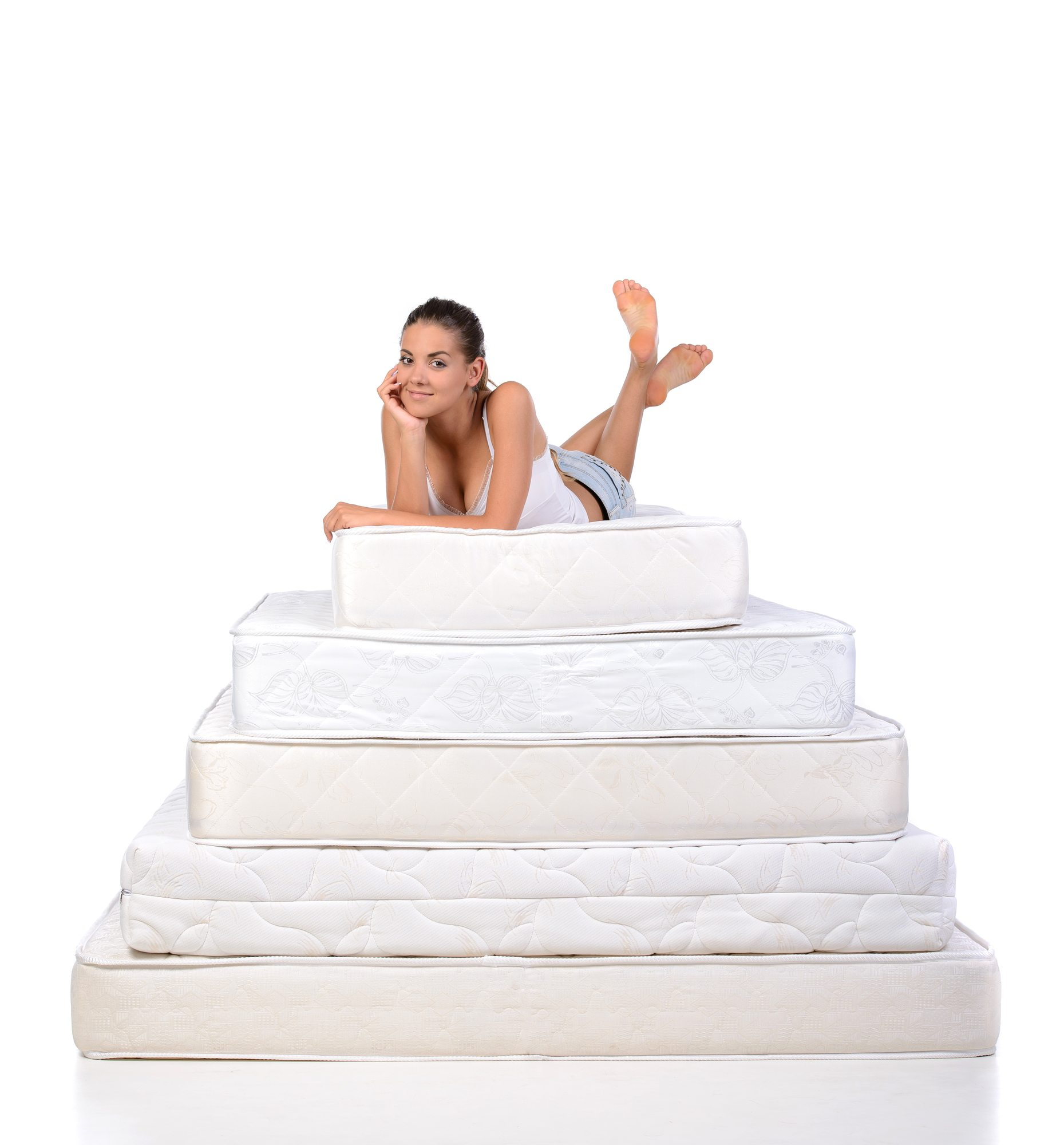 Portrait of a woman lying on many mattresses. Orthopedic mattress.