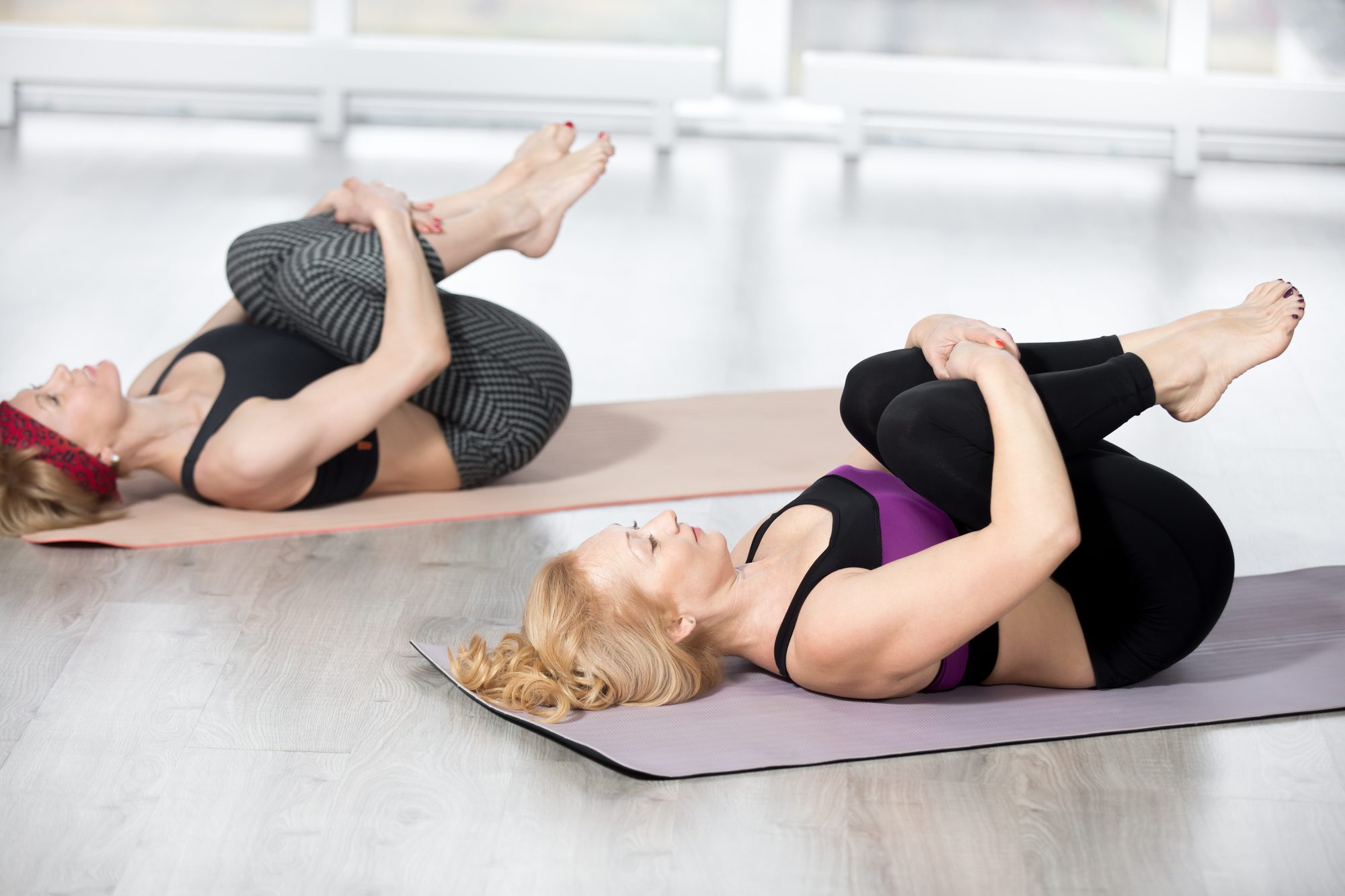 "Fitness, stretching practice, group of two attractive fit mature women working out in sports club, ""warming up"", doing Knees to Chest Pose in class, therapeutic for low back, full length"