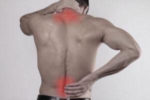 Close up of man rubbing his painful back. Pain relief concept